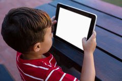 High angle view of boy using digital tablet while sitting at table Royalty Free Stock Photos