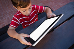 High angle view of boy using tablet while sitting at table Royalty Free Stock Photo