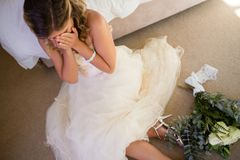 High angle view of bride in wedding dress crying while sitting by bed stock images