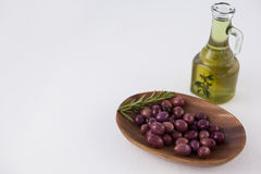 High angle view of brown olives in plate by oil in jar. At table Stock Photography