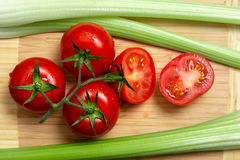 High angle view of bunch of fresh tomatoes and celery sticks Stock Photos
