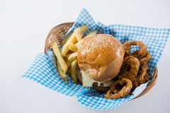 High angle view burger and French fries with onion rings. In wicker basket Stock Image