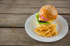 High angle view of burger with French fries served in plate. On wooden table Stock Photography