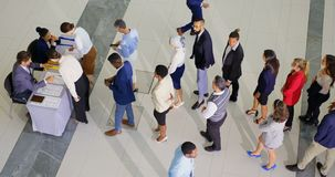 Business people checking in at conference registration table 4k. High angle view of business people standing in line before checking in at the conference stock video footage