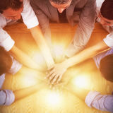 High angle view of business team stacking hands. On table in office Stock Photography