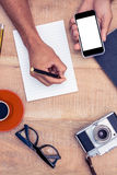 High angle view of businessman hand holding smart phone while writing on notepad. By camera and coffee on table Royalty Free Stock Images
