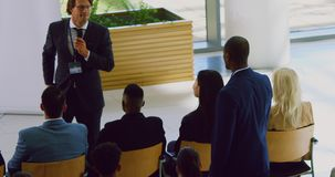 Businessman raising her hand in a business seminar 4k. High angle view of businessman raising her hand in a business seminar. Male speaker interacting with the stock footage