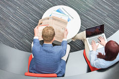 High angle view of businessman reading newspaper while female colleague using laptop in office Stock Images