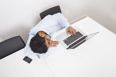 High angle view of businessman sleeping by laptop at desk in office Royalty Free Stock Photography