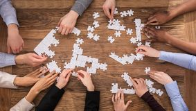 High Angle View Of Businesspeople Solving Jigsaw Puzzle. High Angle View Of Businesspeople Hand Solving Jigsaw Puzzle On Wooden Desk Royalty Free Stock Photos