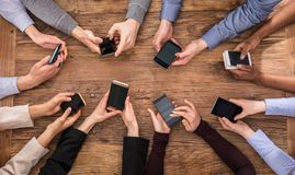 Businesspeople Hand Using Mobile Phone. High Angle View Of Businesspeople Hand Using Mobile Phone Royalty Free Stock Images