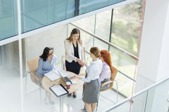 High angle view of businesswomen shaking hands at table in office Royalty Free Stock Image