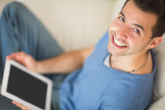 High angle view of casual smiling man using tablet sitting on couch Royalty Free Stock Photography