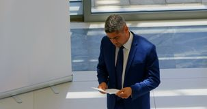 Businessman practicing speech in the office 4k. High angle view of a Caucasian businessman holding his script and practicing speech in the office 4k stock footage
