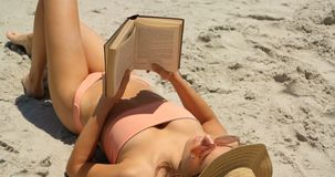 High angle view of Caucasian woman in hat reading a book on the beach 4k stock footage