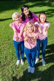 Women in pink t-shirts with ribbons. High angle view of cheerful women in pink t-shirts with ribbons smiling at camera Royalty Free Stock Images