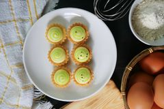 High angle view of cheese tart on white plate. Powder and eggs on black wooden table Stock Photos