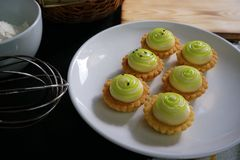 High angle view of cheese tart on white plate. Powder and eggs on black wooden table Stock Image