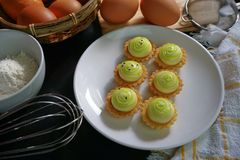 High angle view of delicious cheese tart on white plate. High angle view of cheese tart on white plate. Powder and eggs on black wooden table Royalty Free Stock Photography