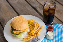 High angle view of cheeseburger and french fries by dip with drink Royalty Free Stock Photography