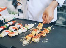 High angle view of chef cooking fresh shrimp BBQ on flat hot plat with one hand holding. Food preparation hand , shrimp , mid section , chef , high angle view Stock Photos