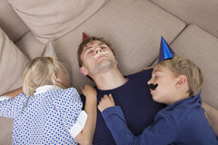 High angle view of children and father with artificial mustache and party hat sleeping on sofa bed Stock Image
