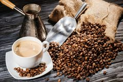 high angle view of coffee cup with scoop and cezve on heap of coffee beans and on rustic stock photos