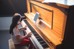 High angle view of concentrated girl practicing piano. High angle view of concentrated girl wearing headphones while practicing piano in classroom at music Stock Photography