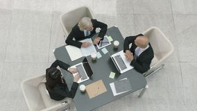 High angle view of corporate executives arriving at business meeting. Three corporate executives in modern company arriving at meeting table to discuss business stock video footage