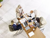 High angle view of corporate executives meeting in office. Four multi-ethnic coporate business people meeting in modern office building, high angle view stock photography