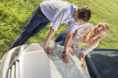 High angle view of couple reading map on car hood during road trip Royalty Free Stock Image
