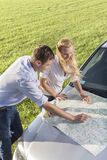 High angle view of couple reading map on car hood during road trip Stock Photography