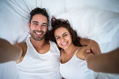High angle view of couple taking self portrait on bed Royalty Free Stock Photos