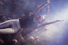 High angle view of crowd lifting female performer at nightclub. During music festival Stock Images
