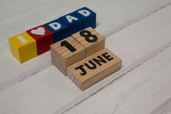 High angle view of cube shapes with text by calender date. On wooden table Royalty Free Stock Photo