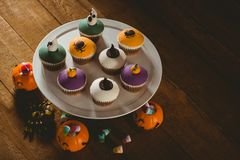 High angle view of cup cakes with decorations during Halloween. High angle view of cup cakes with decorations on wooden table during Halloween Stock Images