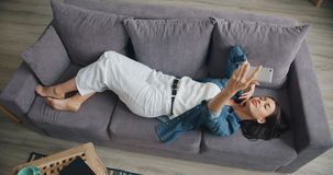High angle view of cute girl taking selfie with smartphone lying on sofa at home. High angle view of cute girl taking selfie with smartphone camera lying on sofa stock footage