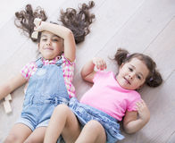 High angle view of cute little sisters lying on wooden floor at home Stock Image