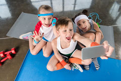 High angle view of cute sporty kids taking selfie with smartphone in gym Royalty Free Stock Photography