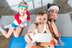 High angle view of cute sporty kids taking selfie with smartphone in gym Royalty Free Stock Images