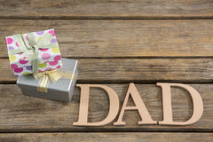 High angle view of dad text by gift boxes on table Royalty Free Stock Image