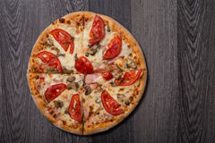 High angle view of delicious Italian pizza with ham and tomatoes Royalty Free Stock Photo