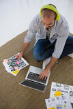 High angle view of designer with collage using laptop while sitting on floor. At studio Stock Images