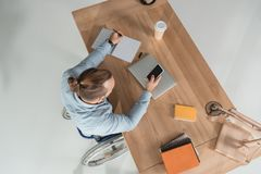 Man on wheelchair using smartphone. High angle view of disabled man on wheelchair using smartphone at workplace in office royalty free stock images