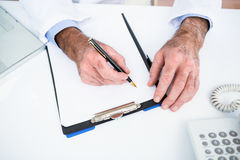 High angle view of doctor writing on paper at clinic Royalty Free Stock Photos