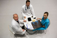 High angle view of doctors and surgeon examining x-ray while having breakfast. In hospital Stock Photography
