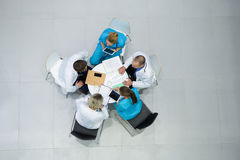 High angle view of doctors and surgeons interacting with each other in meeting Stock Image