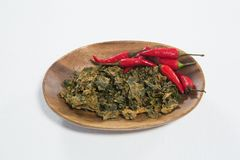 High angle view of dried kale with red chili pepper in wooden plate. Against white backgroundhips on black table at casino Stock Photography