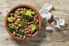 Cooked broad beans and broccoli. High angle view of an earthenware bowl with cooked broad beans and broccoli, on a rustic white wooden table, next to some stock photo