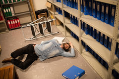 High angle view of fallen businessman and file in storage room Stock Photography